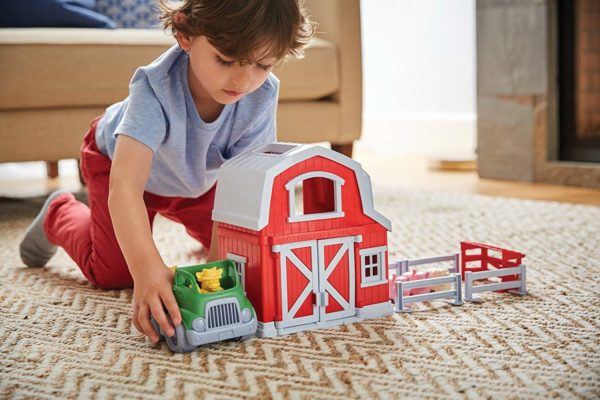 A boy playing with farm playsets