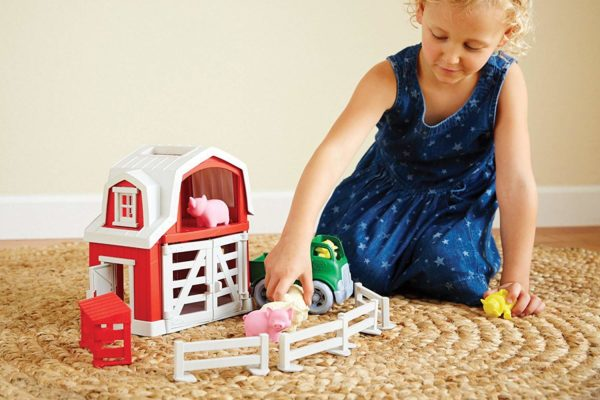 A girl playing with farm playsets